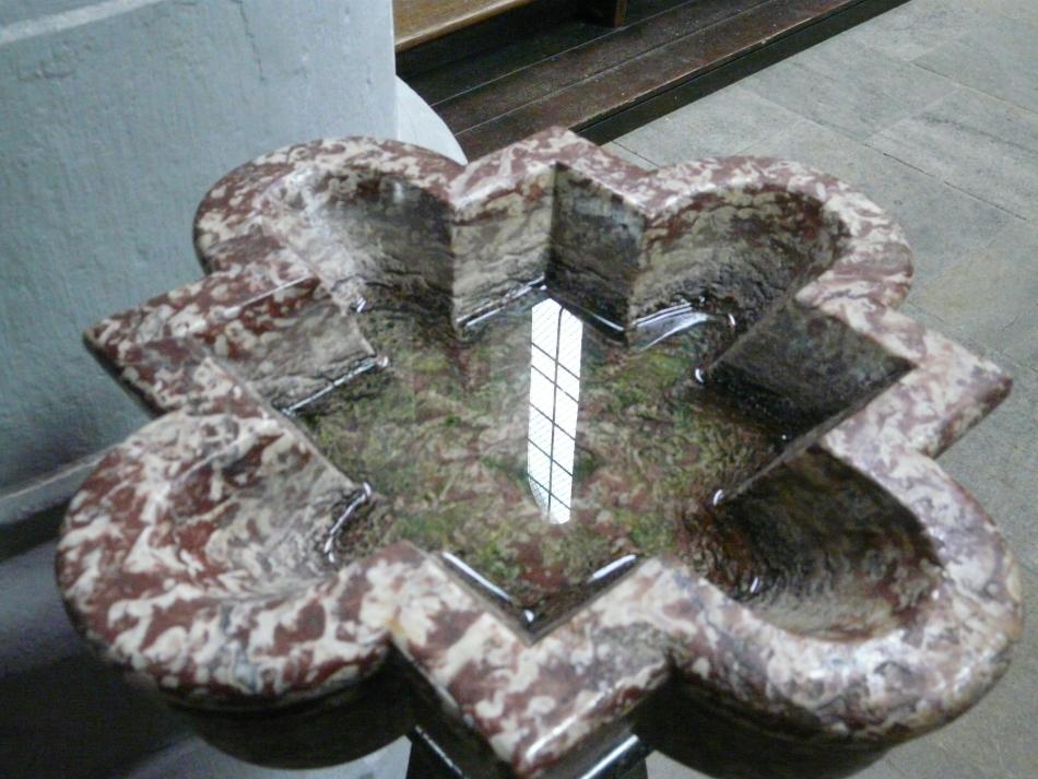 Weihwasserbecken mit Kirchenfensterspiegelung